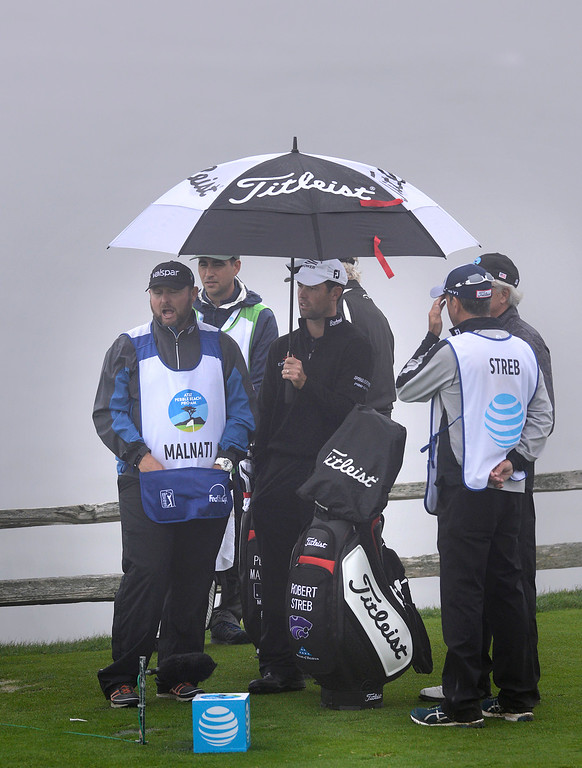 . Robert Streb holds a umbrella with members of his playing group on the seventh tee while waiting for a delay of play due to heavy fog to clear at Pebble Beach Golf Links during the second round of the AT&T Pebble Beach Pro-AM in Pebble Beach on Friday February 10, 2017. (David Royal - Monterey Herald)