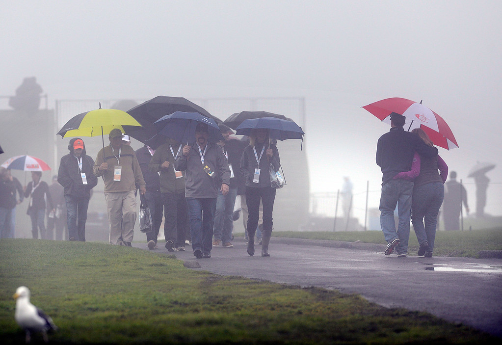 . Golf fans hunker down under umbrellas near the sixth green as a rain squall passes through at Pebble Beach Golf Links during the second round of the AT&T Pebble Beach Pro-AM in Pebble Beach on Friday February 10, 2017. (David Royal - Monterey Herald)