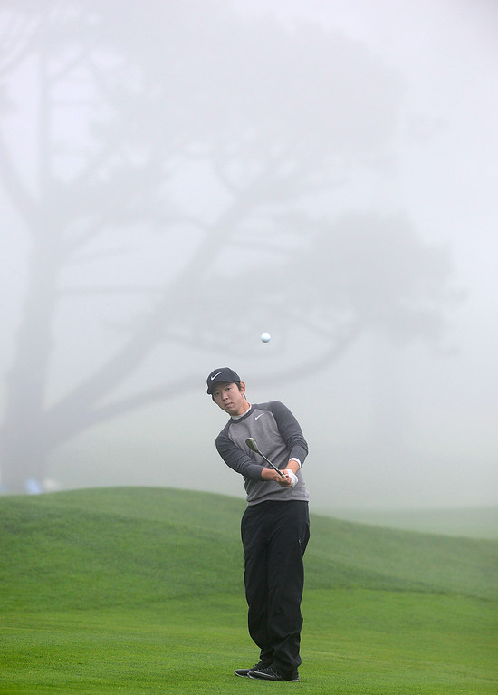 . Seung-Yul Noh chips his ball onto the thirteenth green as a heavy fog rolls in at Pebble Beach Golf Links during the second round of the AT&T Pebble Beach Pro-AM in Pebble Beach on Friday February 10, 2017. (David Royal - Monterey Herald)
