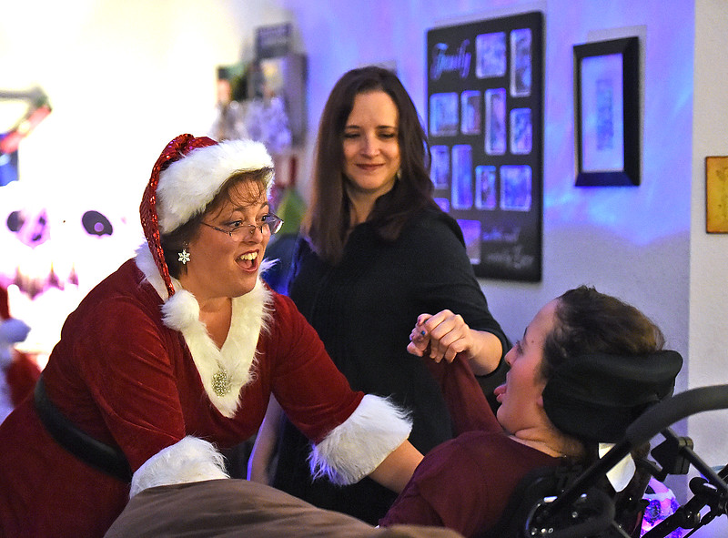 Mrs. Claus dances to a Christmas song with Lily Portillo, 14, and her mom, Sarah Portillo, right during a special visit with her at her Loveland home Sunday, Dec 17, 2017. Portillo started the Secret Sleigh Project, where Santa visits children who have medical issues which make it difficult for them to leave their homes, in 2015 when she realized she wouldn't be able to take Lily to see Santa. (Photo by Jenny Sparks/Loveland Reporter-Herald)