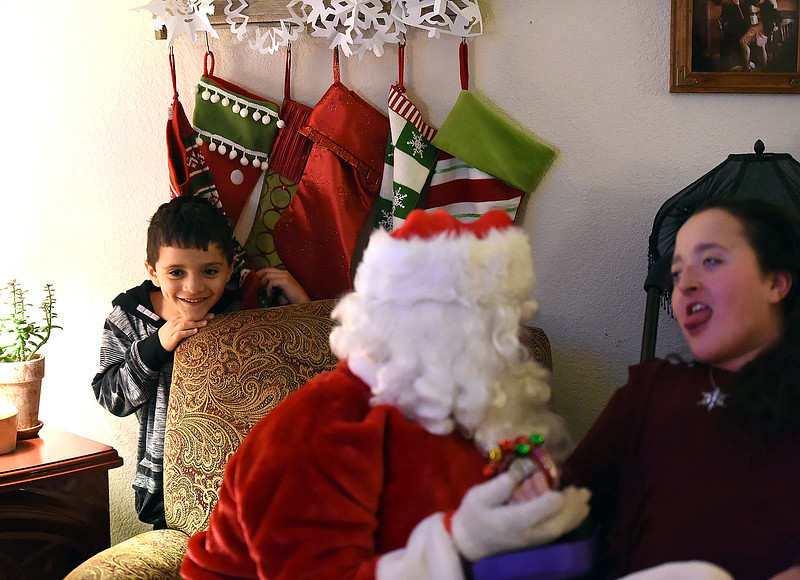 Marcelo Portillo, 7, peeks out from behind a chair and smiles as Santa visits with his big sister Lily Portillo, 14, at her Loveland home on Sunday, Dec 17, 2017. Lily's mom, Sarah Portillo started the Secret Sleigh Project, where Santa visits children who have medical issues which make it difficult for them to leave their homes, in 2015 when she realized she wouldn't be able to take Lily to see Santa. (Photo by Jenny Sparks/Loveland Reporter-Herald)