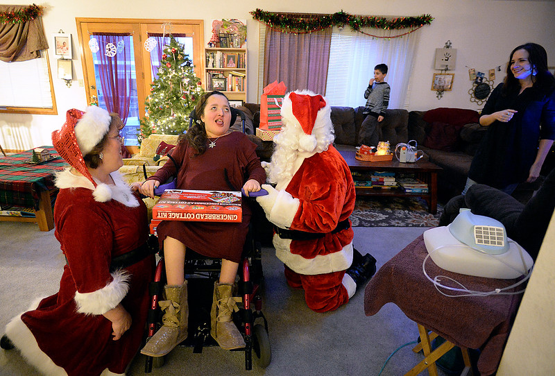 Lily Portillo, 14, smiles as Santa and Mrs. Claus visit with her at her Loveland home as her mom, Sarah Portillo, far right, watches on Sunday, Dec 17, 2017. Portillo started the Secret Sleigh Project, where Santa visits children who have medical issues which make it difficult for them to leave their homes, in 2015 when she realized she wouldn't be able to take Lily to see Santa. (Photo by Jenny Sparks/Loveland Reporter-Herald)