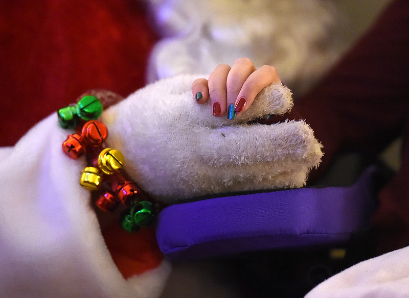 Lily Portillo, 14, holds Santa's hand Sunday, Dec 17, 2017, while he visits her at her Loveland home. Lily's mom, Sarah Portillo started the Secret Sleigh Project, where Santa visits children who have medical issues which make it difficult for them to leave their homes, in 2015 when she realized she wouldn't be able to take Lily to see Santa. (Photo by Jenny Sparks/Loveland Reporter-Herald)