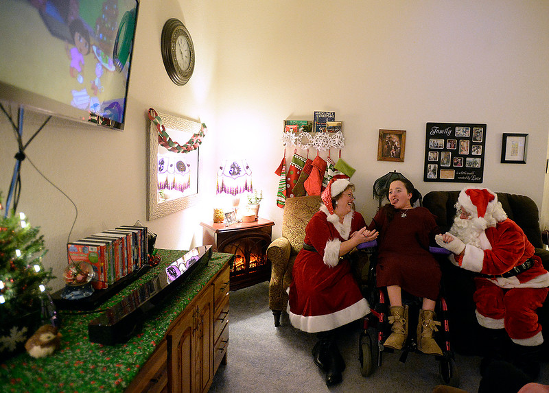 Lily Portillo, 14, smiles as Santa and Mrs. Claus watch one of her favorite Christmas movies with her on Sunday, Dec 17, 2017, at her Loveland home. Lily's mom, Sarah Portillo started the Secret Sleigh Project, where Santa visits children who have medical issues which make it difficult for them to leave their homes, in 2015 when she realized she wouldn't be able to take Lily to see Santa. (Photo by Jenny Sparks/Loveland Reporter-Herald)