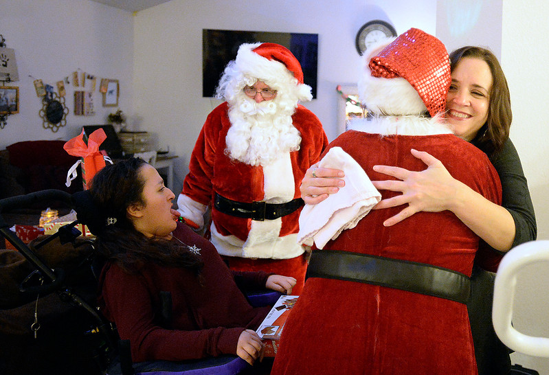 Sarah Portillo, far right, hugs Mrs. Claus as she and Santa visit her daughter, Lily Portillo, 14, at their Loveland home on Sunday, Dec 17, 2017. Portillo started the Secret Sleigh Project, where Santa visits children who have medical issues which make it difficult for them to leave their homes, in 2015 when she realized she wouldn't be able to take Lily to see Santa. (Photo by Jenny Sparks/Loveland Reporter-Herald)
