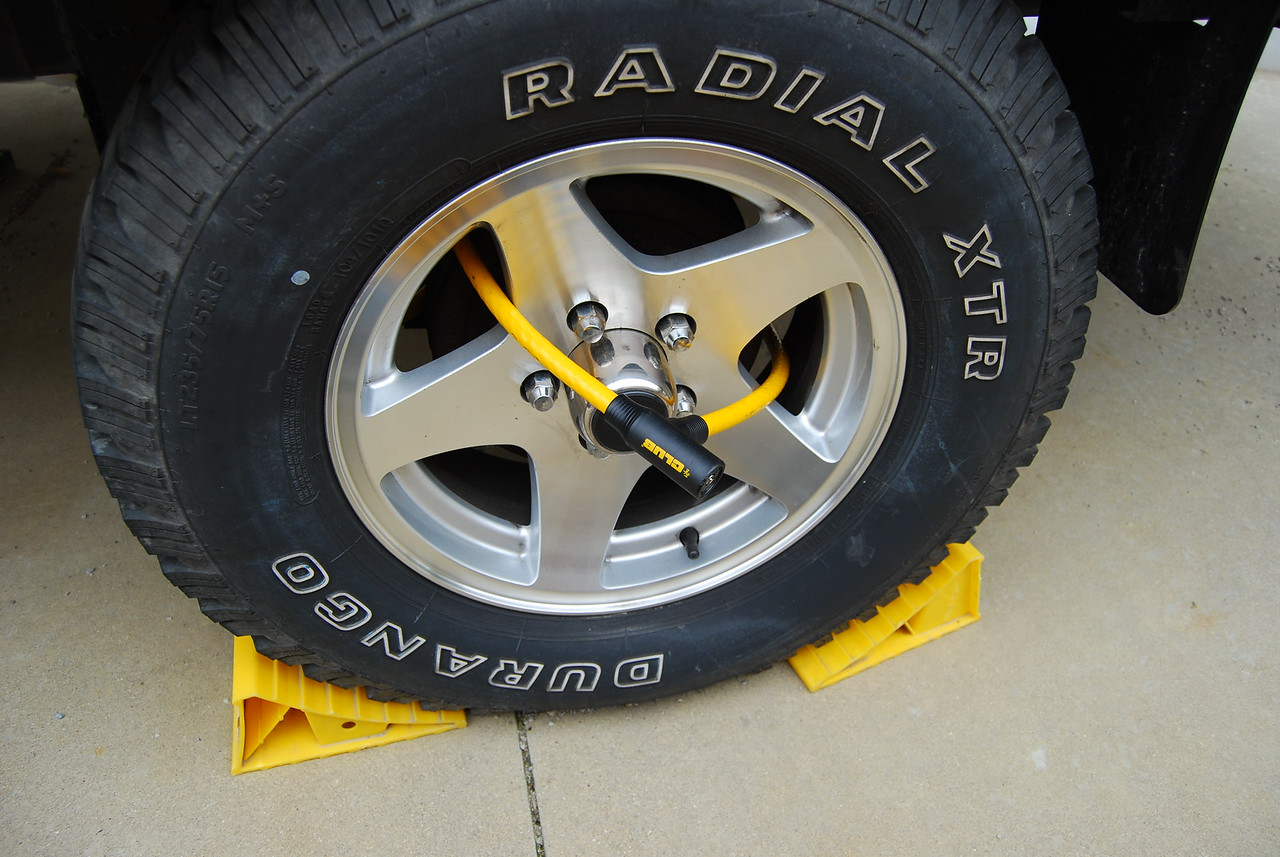 The cable lock goes through the tire and around the axle.