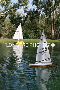 RC Laser sailing on lake along with on of 2 Sabots.