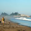 Girl & Dad walking along Maine beach.