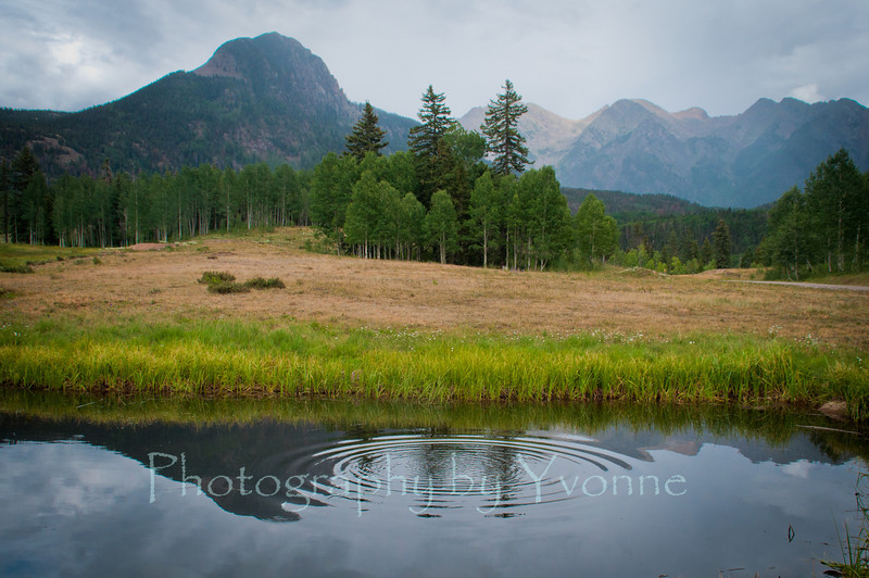 A storm is rolling in over the San Juan Mountains. Spud Mtn. is reflected in the pond as a critter sends out ripples.