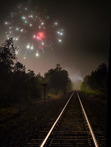 Grand Finale: Looking north along the St. Lawrence and Atlantic railroad tracks, fireworks explode over Oxford Plains Speedway during the final celebration for Oxford Hills graduates.