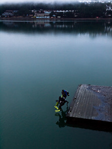 A man and a woman dive into Juneau's waters near where the cruise ships tie up in summer, hoping to find something interesting. They told me the waters are quite full of life, but a little dark and murky sometimes. December 12th, 2009.