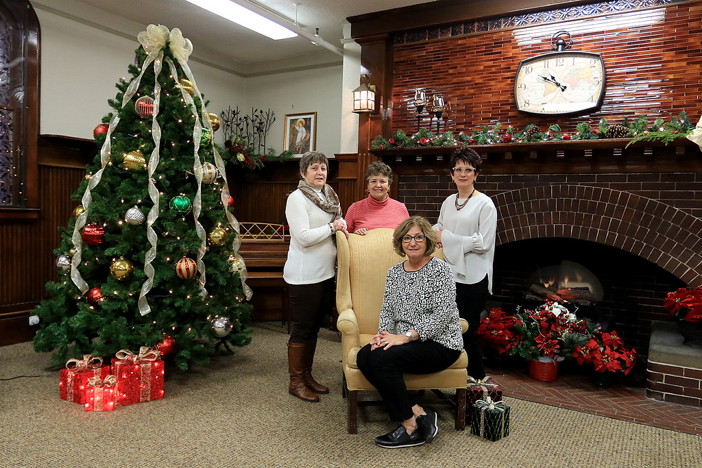 . Fitchburg Senior Center Director Joan Goodwin, sitting, and interior designers Julie Millar with Home Staging by Julie, Diane Walsh, and Susan Campbell with Abracadabra MBA Interiors pose for a picture in the new revamped senior center fireplace room. SENTINEL & ENTERPRISE/JOHN LOVE