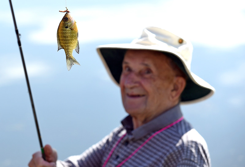 Ninety-three year-old Jean-Jacques Daoust is all smiles Wednesday, Sept. 13, 2017, after catching a blue gill fish during the Senior Fishing Derby put on by the Loveland Fishing Club at River's Edge Natural Area in Loveland.  (Photo by Jenny Sparks/Loveland Reporter-Herald)
