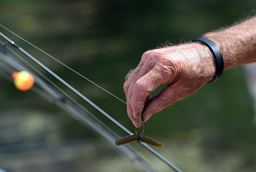 . Lloyd Mobley, left,  puts a rubber worm on his hook for bait after catching a big fish Wednesday, Sept. 13, 2017, during the Senior Fishing Derby put on by the Loveland Fishing Club at River\'s Edge Natural Area in Loveland.  (Photo by Jenny Sparks/Loveland Reporter-Herald)
