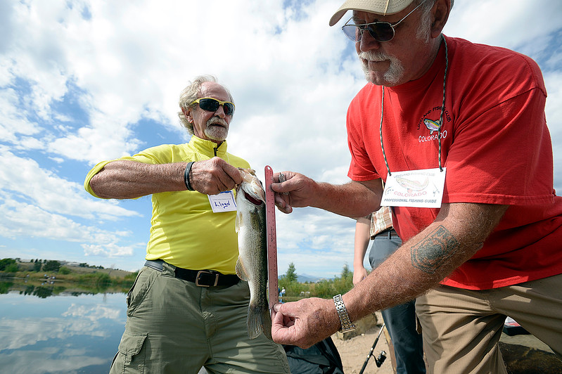 Keith Gentry, a Loveland Fishing Club member, right, measures a largemouth bass caught by Lloyd Mobley, left,  Wednesday, Sept. 13, 2017, during the Senior Fishing Derby put on by the Loveland Fishing Club at River's Edge Natural Area in Loveland.  (Photo by Jenny Sparks/Loveland Reporter-Herald)
