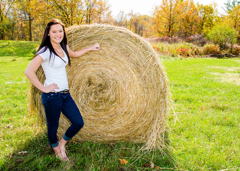 senior portrait of Girl with hay bale