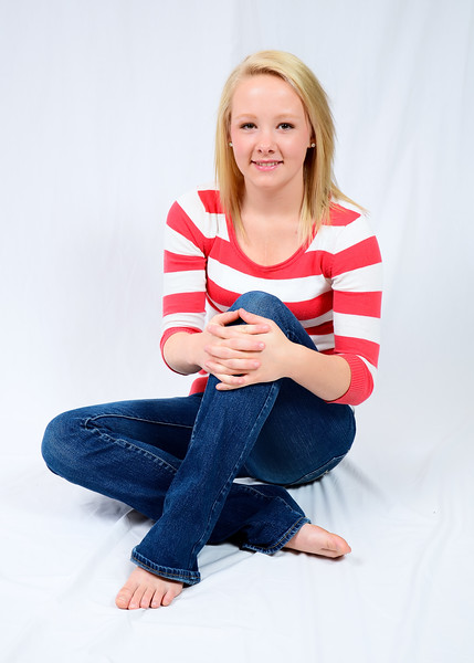Senior portrait of girl with red and white striped shirt sitting