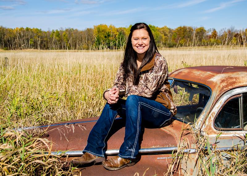 senior portrait of girl sitting on rusty car