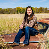 senior portrait of girl sitting on rusty car