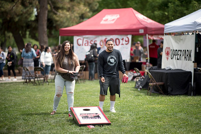 Cinthya Fernandez (left) and Tutulu Finau (right) play corn hole as they enjoy Senior Send-off on Tuesday, April 30, 2019, in Chico, Calif. Students enjoy a free lunch, fun games, and a chance to win exciting prizes including a cruiser bike during the Senior Send-off, sponsored by Chico State Alumni Association. (Jessica Bartlett, University Photographer)