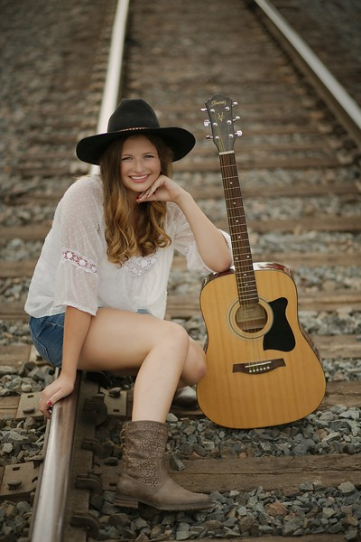 at the tracks with her guitar