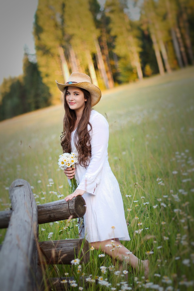 Our cowgirl with the old fence and feild of Daisys