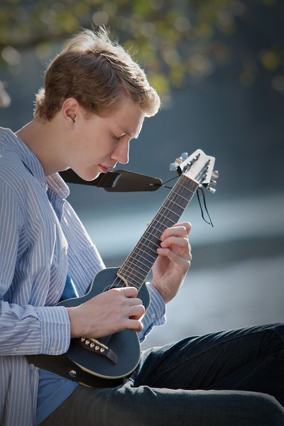 close up shot with Brendan and guitar on the riverbank