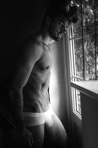 Portrait of handsome man with beard standing next to window with sixpack abs, pecs in his underwear
