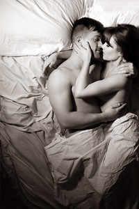 Black and white portrait of naked couple in bed holding each other