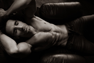 Portrait of attractive shirtless muscular man with beard and sixpack abs lying in leather armchair, sleeping.