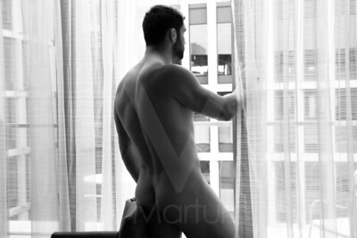 Naked handsome man in hotel room looks out of balcony window