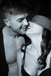Black and white portrait of sexy couple kiss land laugh as female wears blindfold
