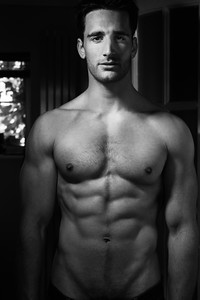 Handsome shirtless man with beard and sixpack abs standing in doorway with unbuttoned jeans