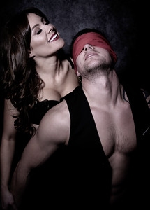 Sexy male and female couple laugh while playing sex game with male blindfolded with red scarf