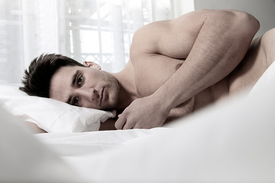 Handsome naked muscular man with beard lying in bed covered with sheet, looking at camera