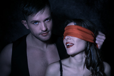 Sexy portrait of male and female couple with male looking at camera while female wears red blindfold and licks her lips
