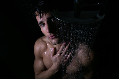 Sexy portrait of handsome naked man with beard and brown eyes under a rainfall shower looking at camera