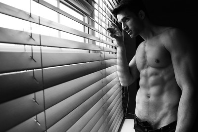 Portrait of handsome man with beard standing next to window with sixpack abs, pecs and unbuttoned jeans