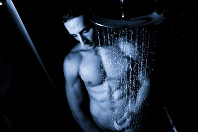 Sexy portrait of handsome naked man with sixpack abs and pecs looking pensive under a rainfall shower