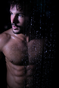 Sexy portrait of handsome naked man with beard, blue eyes and sixpack abs in rainfall shower looking at camera
