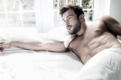 Handsome hairy naked muscular man with beard sixpack abs lying in bed covered with sheet with window in background