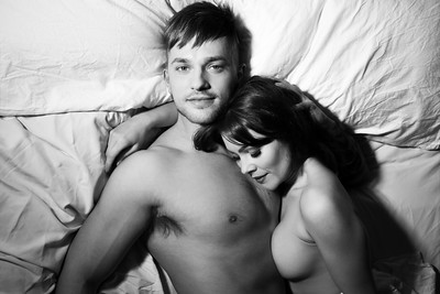 Black and white portrait of naked couple in bed holding each other with man looking up at camera