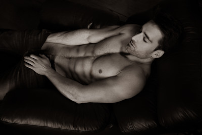 Portrait of attractive shirtless muscular man with beard and sixpack abs lying in leather armchair