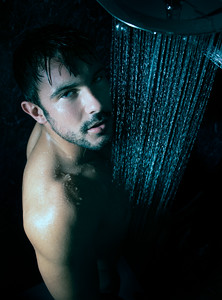 Sexy portrait of handsome naked man with beard and blue eyes under a rainfall shower looking at camera