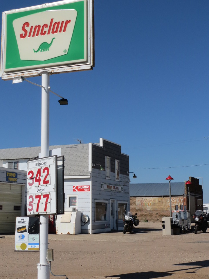 "Day 6 (970 miles):  Park KS.  This old 2 pump gas station is closed on Sundays, so no gas for us, but I did take the opportunity to photograph the iconic Sinclair sign.  I love the simplicity of it.  ""Sinclair.  We sell puree'd dinosaurs.  You want?"""