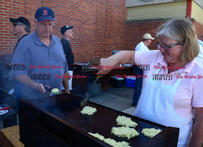 9/16/2016 Mike Orazzi   Staff Andy Helming and Trina Theriault team up while making potato pancakes during Immanuel Lutheran's one day German Festival Saturday in Bristol.