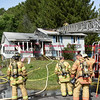 092616  Wesley Bunnell | Staff<br /> <br /> Firefighters in front of 286 Lewis Rd on Monday afternoon after extinguishing the house fire.