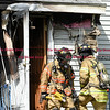 092616  Wesley Bunnell   Staff<br /> <br /> Firefighters cross paths near the front entrance to 286 Lewis Rd in New Britain on Monday afternoon after a home fire was extinguished.