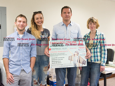 092716  Wesley Bunnell | Staff  Staff of the White Eagle Polish Newspaper stand with a poster for the upcoming First Polish Expo and Job Fair. From left Mikolaj Dabrowski, Alexandra Szynkielewska, Publisher & Co-Owner Darek Barcikowski and Monika Wojcik.