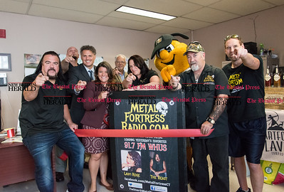 "092716  Wesley Bunnell | Staff  MetalFortressRadio.com WMFR held a ribbon cutting ceremony at his station on Tuesday afternoon.  Far left radio personality Tommy Blando ""The Beast"", State Rep Gary Byron, Mayor Erin Stewart, radio personality Christina Palmer ""Lady Rose"", New Britain Bees Mascot Sting and radio personality Flash Crossfire are shown as everyone points to the camera."